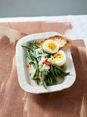 Spicy coconut beans with a boiled egg and grilled baguette