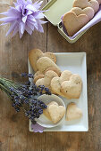 Heart-shaped, gluten-free lavender shortbread biscuits on a serving platter and in a biscuit tin