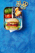 Lunchbox with mini cheeseburger subs, fresh fruits and vegetable