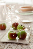 Apples tied with string as festive table decorations