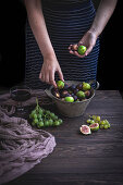 Woman picking up fresh figs from a bucket on a rustic wooden table