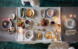 A table laid for Christmas dinner with fairy lights and a fruit bowl