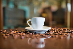 Ceramic cup on round saucer among roasted coffee beans on wooden table