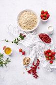 Zutaten für gesundes Frühstück: Haferflocken, Erdbeeren und rote Johannisbeeren