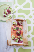 Salmon fillet with onions and broccoli in parchment paper