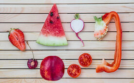 Flatlay of colorful red fruits and vegetables arranged on a wooden background