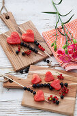 Fruit skewers of melon hearts and currants