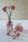Garlic bulbs, pickled garlic and vase of carnations
