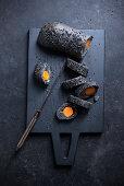 Schwarzes Sesambaguette mit eingebackener Karotte.