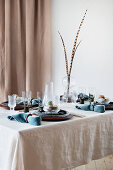 Pheasant feathers on table set in blue and natural shades