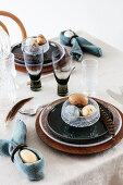 Gedeckter Tisch in Blau und Naturtönen mit Fasanenfedern