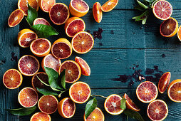 Halved blood oranges with leaves on a blue wooden surface