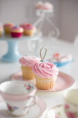Cupcakes with pink frosting on table set in romantic style