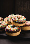 Oven-baked vegan donuts with dark chocolate icing and colourful sprinkles