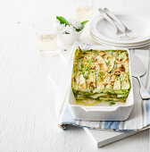 Green lasagna with brie cheese, zucchini and pine nuts
