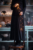 Woman holding illuminated string of fairy lights