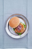 Eggplant and rice burger with red onions in a bun