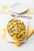 Penne casserole with cooked ham, fava beans and scamorza