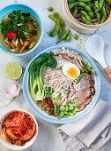 Asian noodle soup with kimchi, edamame, pork, egg, coriander, leek and pak choi