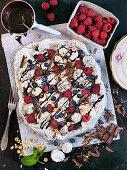 Pavlova with summer berries, hazelnuts and chocolate sauce