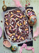 Easter chocolate brittle with chocolate eggs, pieces of chocolate and candy sprinkles