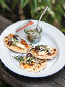 Wholemeal mini pizzas with cheese, herb and onion salsa and olives