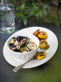 Grilled mussels in parchment paper with grilled corn and vegetables