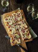Tarte flambée with bacon and onions on a wooden board with three glasses of wine