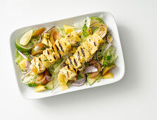 Grilled chicken and pineapple skewers on a mixed leaf salad