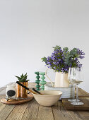 Simple kitchen utensils and jug of flowers on wooden table