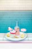 Summery pink cocktail with candy floss next to swimming pool