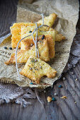 Cheese pastries with peppercorns on newspaper