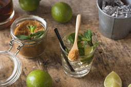 Fresh limes and peppermint leaves, rum and brown sugar for mojito preparation
