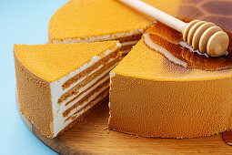 Honey spoon on honeycomb cake