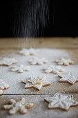 Dusting snowflake cookies with powdered sugar