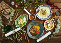 Green plant twigs placed around various tasty dishes on wooden tabletop
