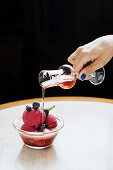 Woman pouring a red beverage on purple scoops of ice cream in bowl with fresh blueberry and mint