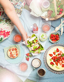 A picnic with strawberry cake, baguettes, quiches and smoothies