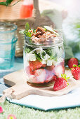 Salad with strawberries, feta and arugula in a glass for a picnic