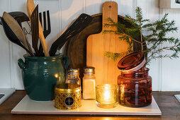 Kitchen utensils, candle lantern and conifer branch