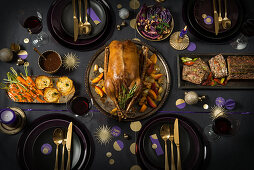 A table laid for Christmas with goose, vegetarian nut loaf, potato gratin, carrots and red cabbage
