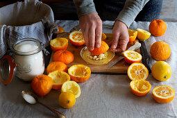 Preparing orange jam from Seville oranges: squeezing out the juice