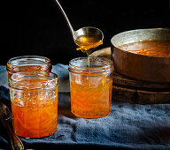 Pouring orange jam from Seville oranges into glasses
