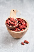 Goji berries in a wooden bowl and a wooden scoop