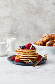 A stack of pancakes served with summer berries