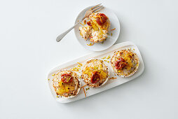 Cream cheese tartlets with dried tomatoes, pistachios, orange zest and honey