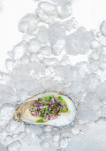 An open oyster with chives and onions on ice