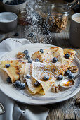 Crepes with blueberries, walnuts, honey and icing sugar for breakfast