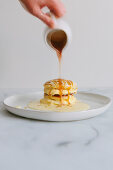 Pouring caramel sauce over Japanese soufflé pancakes