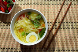 Oriental ramen healthy noodles soup with shiitake, spinach, carrots, eggs and chillies